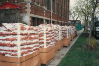 A semi truckload of totes of 10 pound bags of potatoes line the sidewalk for the Easter Holiday GiveAway.